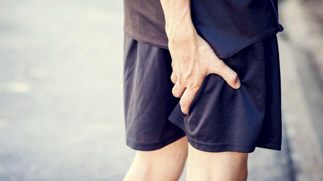 Das Bild zeigt einen Läufer, der sich seinen schmerzenden Oberschenkel hält.