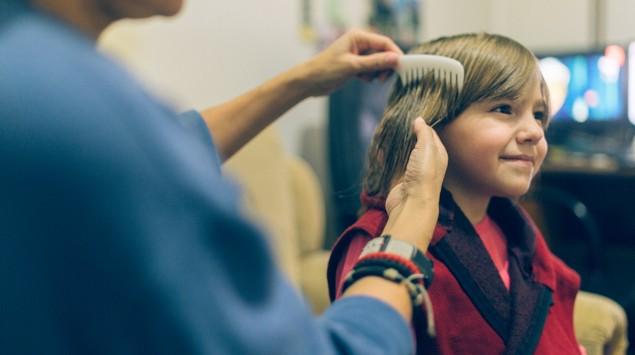 Jemand kämmt einem Kind die Haare mit einem Läusekamm.