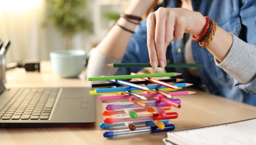 Eine Frau sitzt am Schreibtisch und baut einen Turm aus Stiften.