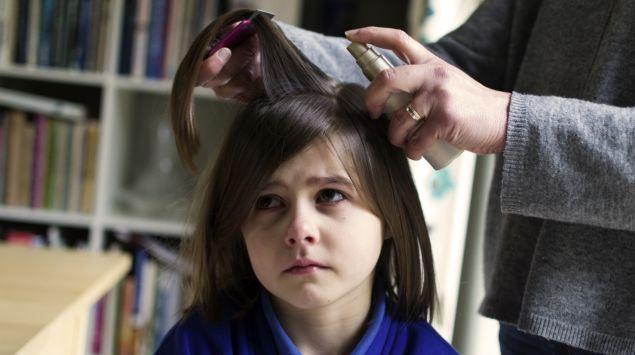 Ein Kind wird gegen Läuse behandelt.