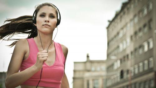 Das Bild zeigt eine junge Frau, die beim Laufen Musik hört.