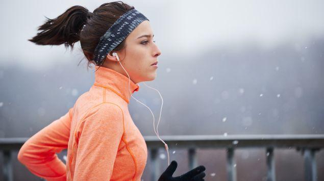 Das Bild zeigt eine Frau, die im Winter joggt.