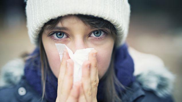 Junge Frau mit Taschentuch und laufender Nase.