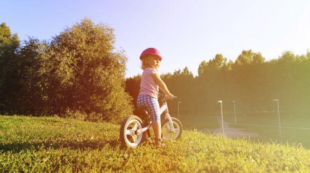 Ein kleines Mädchen mit Helm auf einem Laufrad.