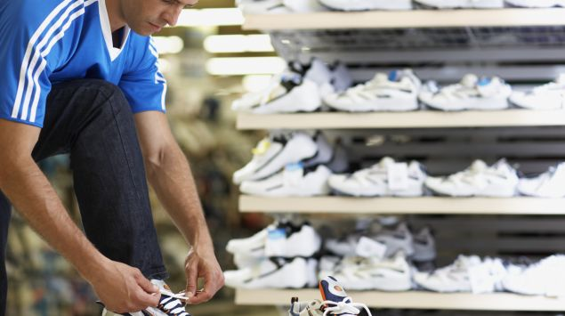 Das Bild zeigt einen Mann, der sich ein Paar Laufschuhe anzieht.