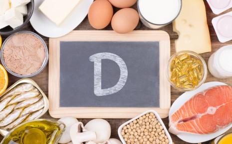Vitamin D: Man sieht verschiedene Lebensmittel und eine Schiefertafel mit einem großen D.