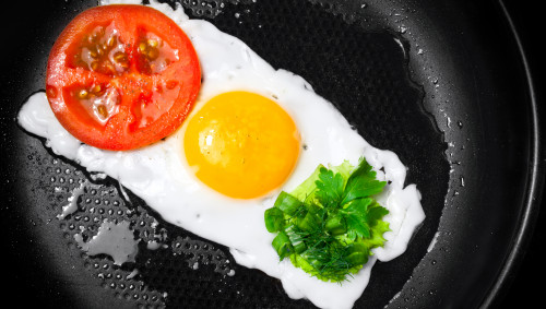 Ein Spiegelei bildet mit Tomate und Petersilie eine Lebensmittelampel