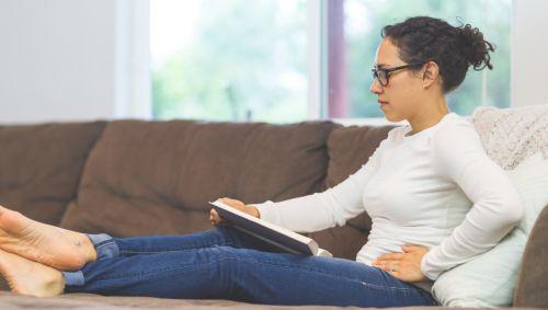 Eine Frau sitzt auf dem Sofa und hält sich mit einer Hand die Leiste.