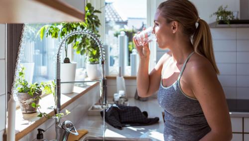 Eine Frau steht in der Küche und trinkt ein Glas Leitungswasser.