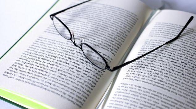 Eine Brille liegt auf einem aufgeschlagenen Buch.