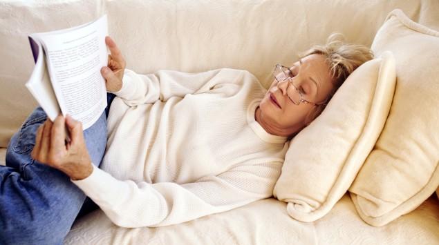 Eine Frau liegt auf dem Sofa und liest ein Buch.