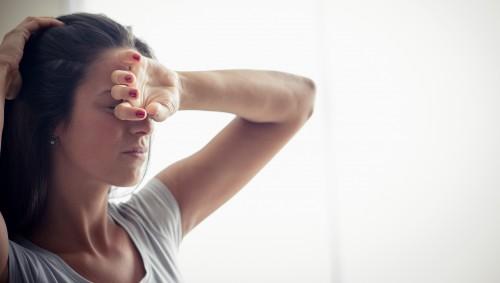 Eine junge Frau schirmt ihre Augen mit der Hand vor dem durchs Fenster fallenden Licht ab.