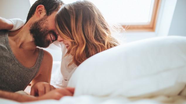 Ein junges Paar küsst sich im Bett.