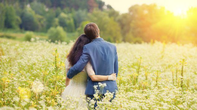 Man sieht ein junges Paar auf einer blühenden Wiese.