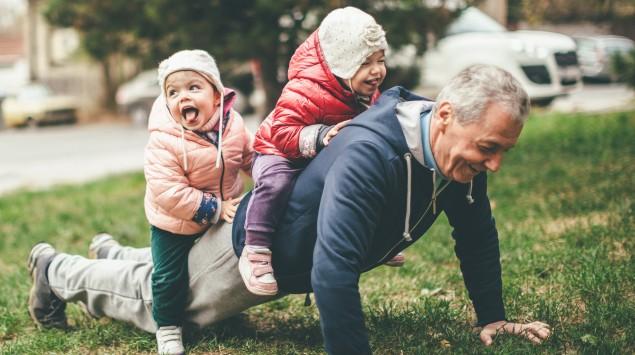 Opa macht mit Enkeln auf dem Rücken Liegestützen