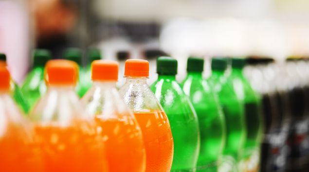 Zu sehen sind in Reihe angeordnete, verschiedenfarbige PET-Limonadenflaschen.