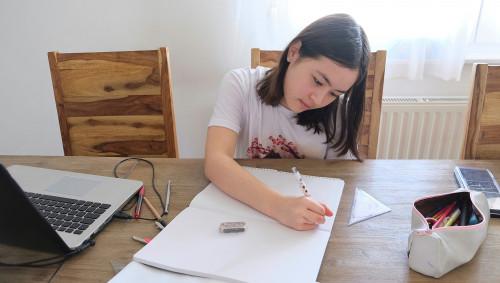Ein Mädchen schreibt mit der linken Hand auf Papier.