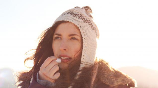 Das Bild zeigt eine Frau, die einen Lippenpflegestift benutzt.