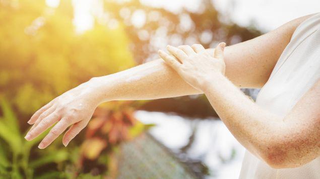 Eine Frau cremt sich die Arme ein.