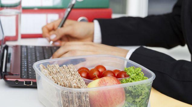 Man sieht eine Lunchbox mit Knäckebrot, Salat, Tomaten und Apfel.