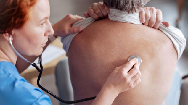 Ein Arzt hört bei einer Frau die Lunge ab.