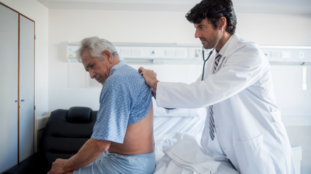 Ein Arzt hört die Lunge eines Mannes ab. Covid-19 verursacht Lungenentzündungen.