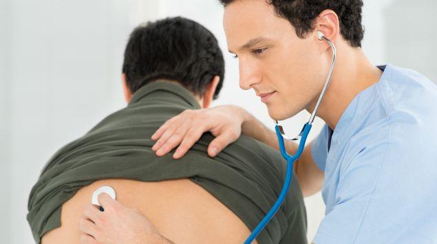 Ein Arzt hört die Lunge eines Mannes ab.