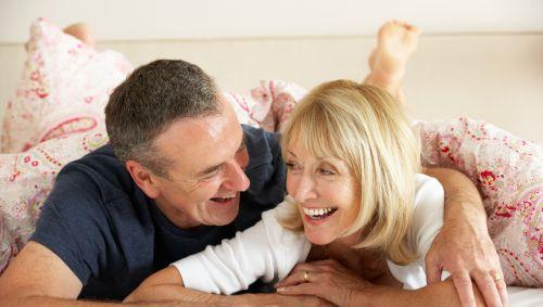 Älteres Ehepaar liegt im Bett und lacht