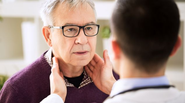 Ein Arzt tastet beim Patienten die Lymphknoten ab.