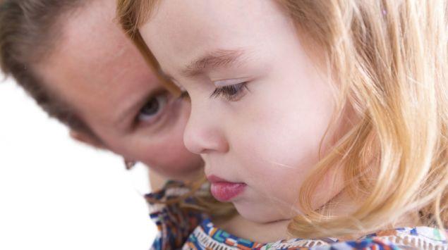 Eine Mutter kniet neben einem kleinen Mädchen