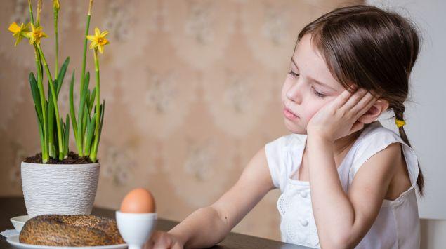 Ein Mädchen sitzt lustlos am Frühstückstisch.
