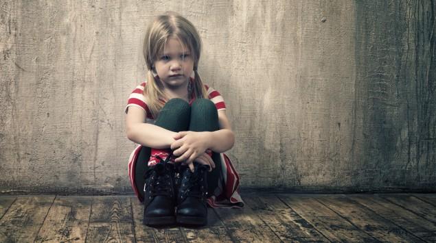 Ein kleines Mädchen sitzt an einer Wand.