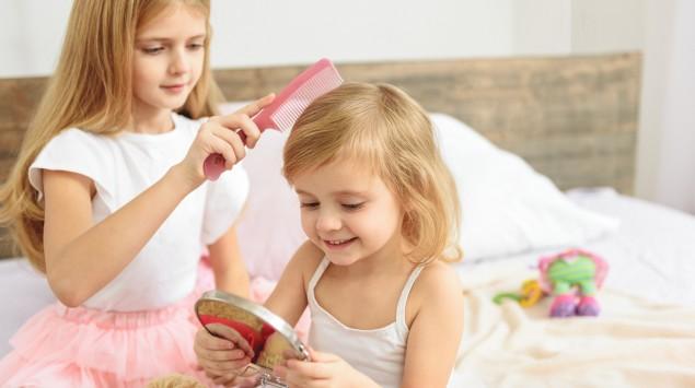 Ein Mädchen kämmt ihre jüngere Schwester.