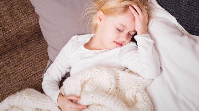 Ein kleine Mädchen liegt auf dem Sofa und hat Kopfschmerzen.