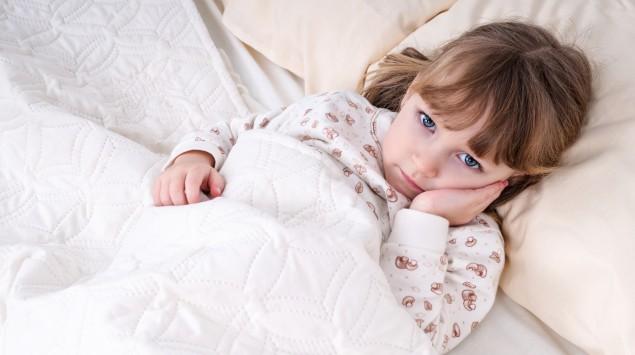 Ein Mädchen liegt krank im Bett und hält sich die Wange.