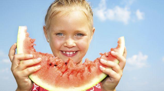 Ein kleines Mädchen isst ein Stück Melone