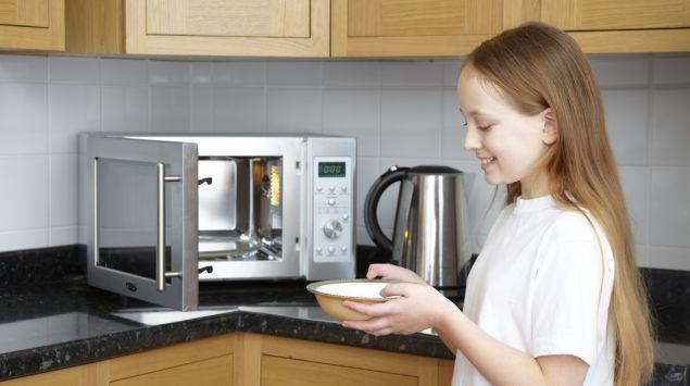 Ein Mädchen benutzt die Mikrowelle.