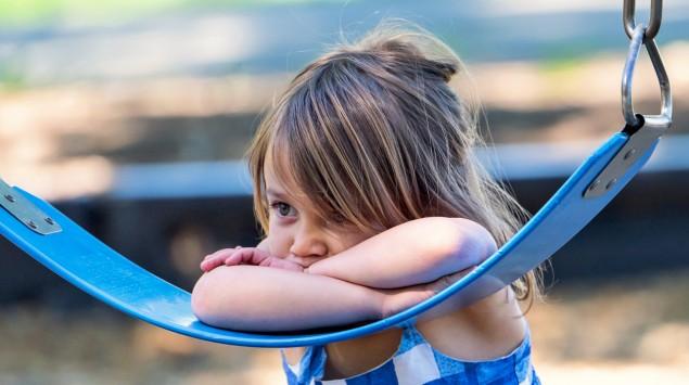 Ein traurig aussehendes Mädchen an einer Schaukel.