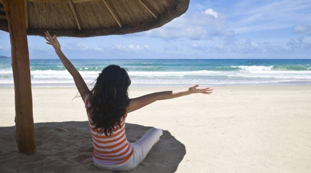 Ein Mädchen sitzt am Strand unter einem Sonnenschirm.