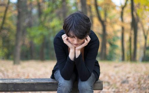 Ein Mädchen sitzt allein auf einer Bank am Waldrand, die Ellenbogen auf die Knie und den Kopf auf die Hände gestützt.