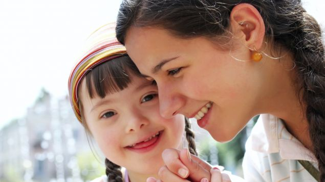 Man sieht ein Mädchen mit Down-Syndrom mit seiner Mutter.