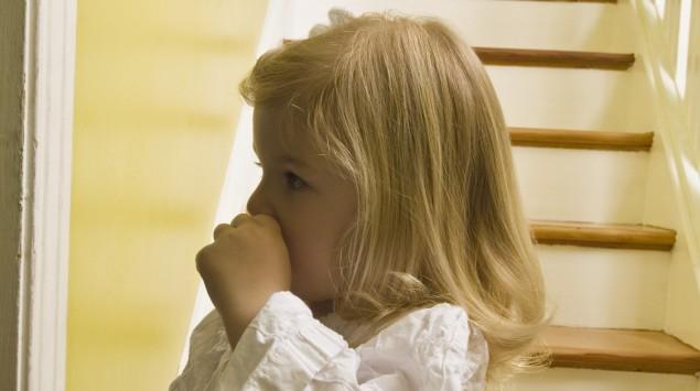 Das Bild zeigt ein am Daumen nuckelndes Mädchen in einem Nachthemd.