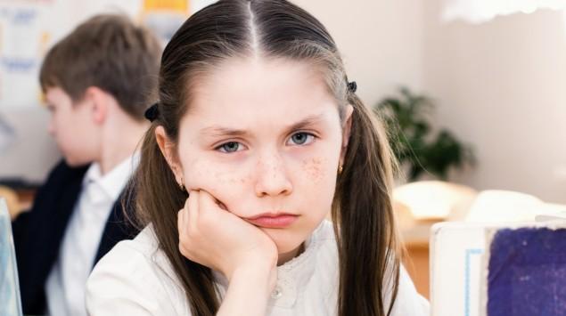 Das Bild zeigt ein trauriges Mädchen in der Schule.
