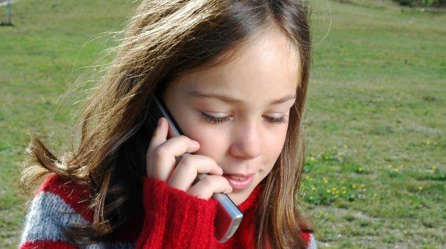 Ein Mädchen telefoniert draußen mit einem Mobiltelefon.
