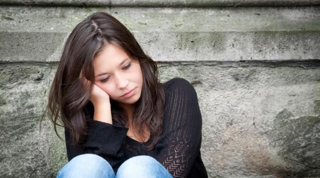 Ein traurig wirkendes Mädchen im Teenageralter sitzt auf einer Steintreppe.