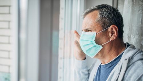 Ein Mann mit Mundschutz schaut nach draußen
