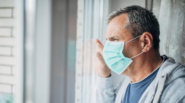 Ein Mann mit Mundschutz schaut aus dem Fenster