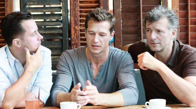 Das Bild zeigt drei Männer im Cafe, die sich unterhalten.
