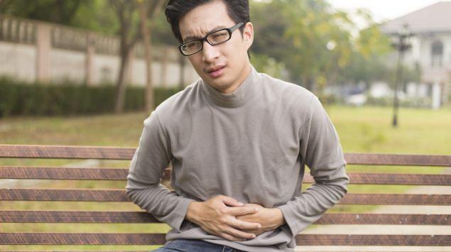 Ein Mann sitzt auf einer Parkbank und hält sich den Bauch.
