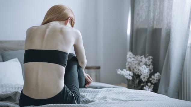 Ein magersüchtiges Mädchen sitzt auf dem Bett.
